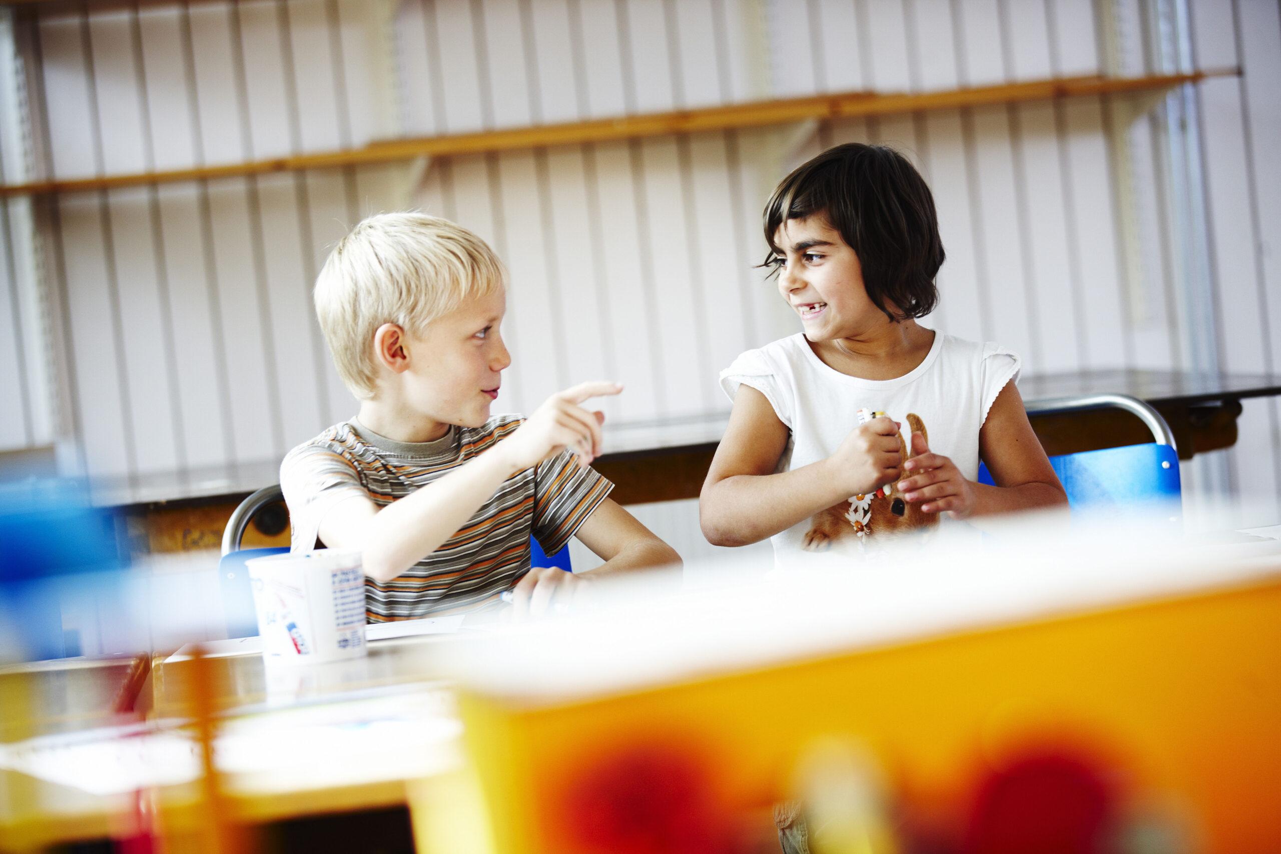 Ett fotografi av två barn som sitter vid ett bord.