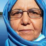 Fotografi av en kvinna med glasögon och blå slöja.